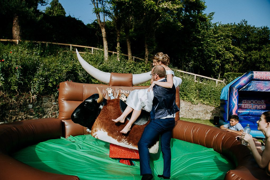 Groom helping bride on to bucking bronco