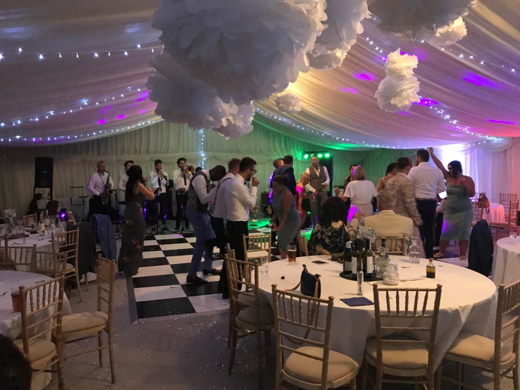 guests dancing in the evening in the marquee